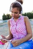 Belle jeune femme écoutant la musique avec le comprimé numérique dedans Photo libre de droits