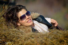 Belle jeune femme détendant sur la pile de foin Photographie stock libre de droits