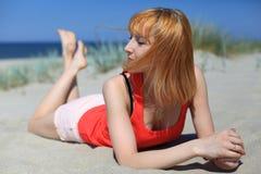 Belle jeune femme détendant sur la plage Photographie stock libre de droits