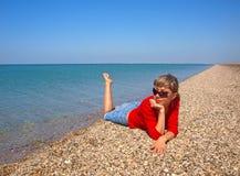 Belle jeune femme détendant sur un littoral photo stock