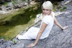 Belle jeune femme détendant sur une roche Photo libre de droits