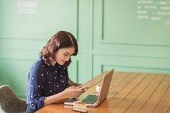 Belle jeune femme d'affaires asiatique mignonne dans le café, m'envoyant Image libre de droits