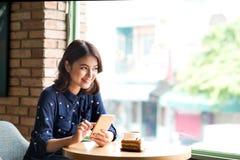 Belle jeune femme d'affaires asiatique mignonne dans le café, utilisant le mobi Photos stock