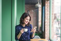 Belle jeune femme d'affaires asiatique mignonne dans le café, utilisant le mobi photo libre de droits