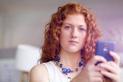 Belle jeune femme d'affaires heureuse employant le sourire futé de téléphone photo stock