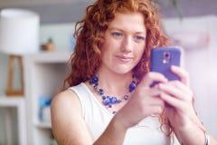Belle jeune femme d'affaires heureuse employant le sourire futé de téléphone image libre de droits