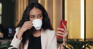 Belle jeune femme d'affaires s'asseyant en bureau ou café moderne et parlant par la vidéo-causerie dans le smartphone Elle rit banque de vidéos