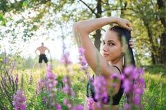 Belle jeune femme d'ajustement dans l'équipement sportif dans l'herbe grande verte Photographie stock