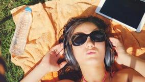 Belle jeune femme dans des lunettes de soleil se trouvant sur l'herbe, écoutant la musique et la chanson de chant Photographie stock libre de droits