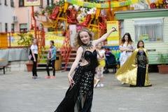Belle jeune femme dans des v?tements d'un style occasionnel d'isolement au-dessus du fond blanc Danse de jeune fille dans la dans photo libre de droits
