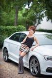 Belle jeune femme dans l'équipement sexy se tenant à la voiture blanche Photos libres de droits