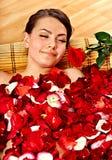 Belle jeune femme dans l'eau de bain de pétale de rose. Photographie stock libre de droits