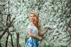 Belle jeune femme dans la maxi jupe florale marchant dans le jardin de floraison de ressort image libre de droits