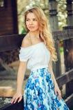 Belle jeune femme dans la maxi jupe florale marchant dans le jardin de floraison de ressort photos libres de droits