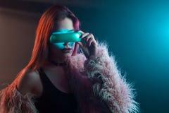 Belle jeune femme dans la réalité virtuelle futuriste en verre, style de Cyberpunk, lampe au néon Photos stock