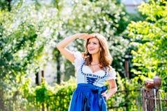 Belle jeune femme dans la robe bavaroise traditionnelle en parc images stock