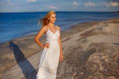 Belle jeune femme dans la robe blanche par la mer au soleil photos stock
