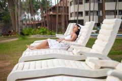 Belle jeune femme dans la robe blanche se trouvant sur un canapé du soleil par la mer Concept de voyage et d'?t? image stock