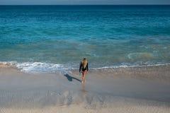 Belle jeune femme dans le bikini avec le panneau de ressac à la plage de l'île tropicale Image stock
