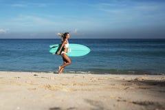 Belle jeune femme dans le bikini avec le panneau de ressac à la plage de l'île tropicale Photographie stock