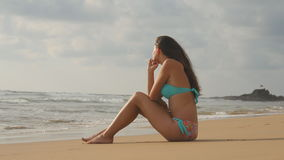 Belle jeune femme dans le bikini se reposant sur le sable d'or sur la plage de mer Fille bronzée détendant sur le rivage parfait  Photos libres de droits