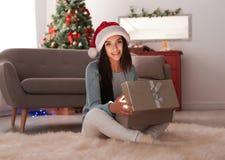 Belle jeune femme dans le boîte-cadeau de Noël d'ouverture de chapeau de Santa Photos libres de droits
