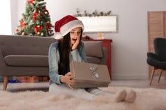 Belle jeune femme dans le boîte-cadeau de Noël d'ouverture de chapeau de Santa Photo libre de droits