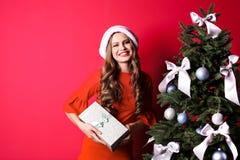 Belle jeune femme dans le chapeau de Santa avec le boîte-cadeau près de l'arbre de Noël Photo stock