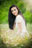 Belle jeune femme dans le domaine de fleurs sauvages Portrait de fille attirante de brune avec de longs cheveux détendant en natu Photo stock