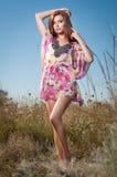 Belle jeune femme dans le domaine de fleurs sauvages sur le fond de ciel bleu Portrait de fille rouge attirante de cheveux avec l Photographie stock libre de droits