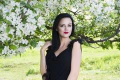 Belle jeune femme dans le jardin de floraison de ressort avec les fleurs blanches, maquillage professionnel photographie stock