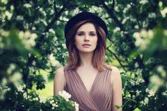 Belle jeune femme dans le jardin des fleurs d'Apple image stock