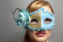 Belle jeune femme dans le masque vénitien mystérieux sur le gris photos libres de droits