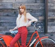 Belle jeune femme dans le pantalon en twill rouge tenant des mains sur sa bicyclette de vintage et regardant l'appareil-photo ave Photos stock
