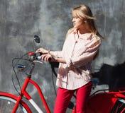 Belle jeune femme dans le pantalon en twill rouge tenant des mains sur sa bicyclette rouge de vintage, se tenant contre le mur gr Photos stock