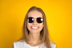 Belle jeune femme dans le sourire de lunettes de soleil d'isolement sur le fond jaune image libre de droits