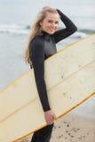 Belle jeune femme dans le vêtement isothermique tenant la planche de surf à la plage Photographie stock libre de droits
