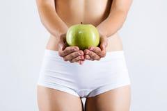 Belle jeune femme dans les sous-vêtements blancs tenant la pomme verte Photographie stock