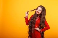 Belle jeune femme dans Mini Dress rouge Studio tiré sur le fond jaune photographie stock libre de droits