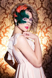 Belle jeune femme dans un masque vénitien mystérieux vert un carnaval de nouvelle année, mascarade de Noël, un club de danse, sec Photographie stock