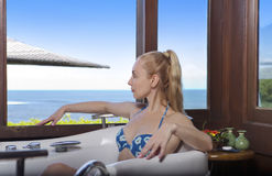 Belle jeune femme dans une grande baignoire de hydromassage près d'une fenêtre donnant sur la mer Image libre de droits
