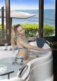 Belle jeune femme dans une grande baignoire de hydromassage près d'une fenêtre donnant sur la mer Photos libres de droits