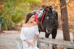 Belle jeune femme dans une longue robe blanche avec le cheval brun extérieur Photographie stock
