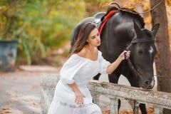 Belle jeune femme dans une longue robe blanche avec le cheval brun extérieur Image libre de droits