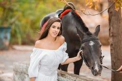 Belle jeune femme dans une longue robe blanche avec le cheval brun extérieur Photo stock