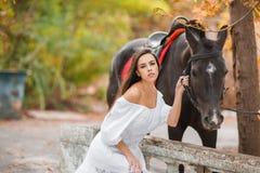 Belle jeune femme dans une longue robe blanche avec le cheval brun extérieur Images libres de droits