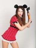 Belle jeune femme dans une robe courte avec des points de polka, dans sa main tenant la hache Image stock