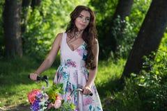 Belle jeune femme dans une robe et un chapeau sur une bicyclette sur le national Image stock