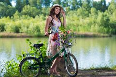 Belle jeune femme dans une robe et un chapeau sur une bicyclette sur le national Photo stock