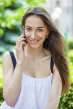 Belle jeune femme de brune appelant par le téléphone photo stock